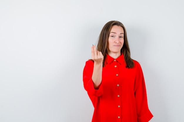 Mujer joven haciendo gesto de dinero en blusa roja y mirando disgustado. vista frontal.