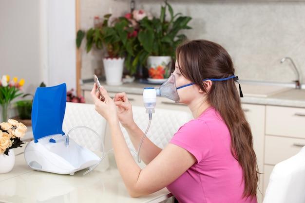Mujer joven haciendo inhalación con un nebulizador en casa