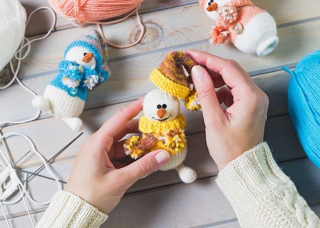 Mujer joven haciendo juguetes artesanales de navidad sobre mesa de madera