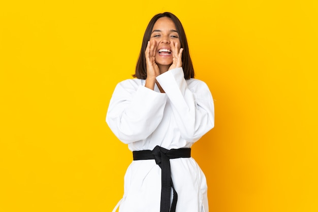 Mujer joven haciendo karate aislado en la pared amarilla gritando y anunciando algo