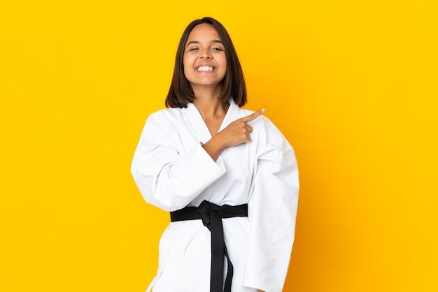 Mujer joven haciendo karate aislado sobre fondo amarillo apuntando hacia el lado para presentar un producto