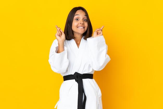 Mujer joven haciendo karate aislado sobre fondo amarillo con los dedos cruzados