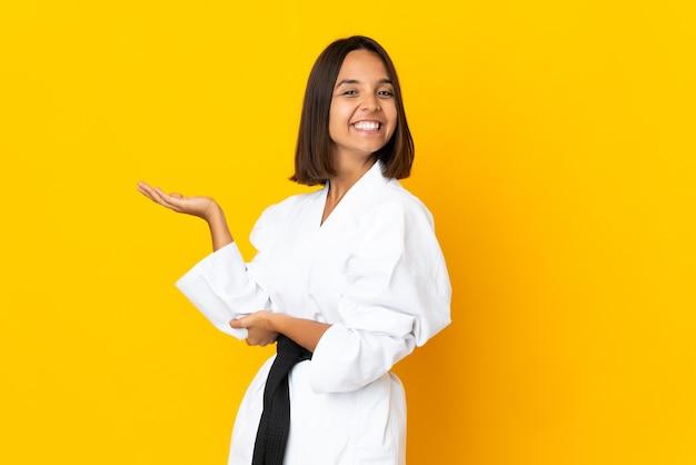Mujer joven haciendo karate aislado sobre fondo amarillo extendiendo las manos hacia el lado para invitar a venir