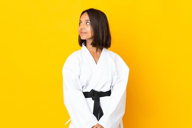 Mujer joven haciendo karate aislado sobre fondo amarillo mirando hacia el lado