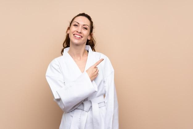 Mujer joven haciendo karate apuntando hacia un lado para presentar un producto