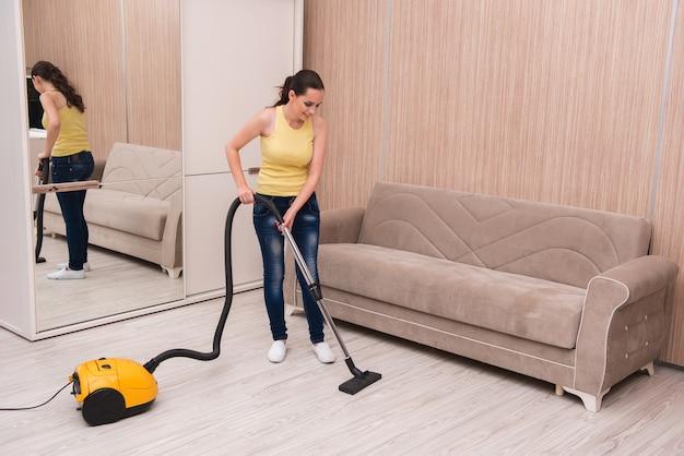 Mujer joven haciendo limpieza en casa