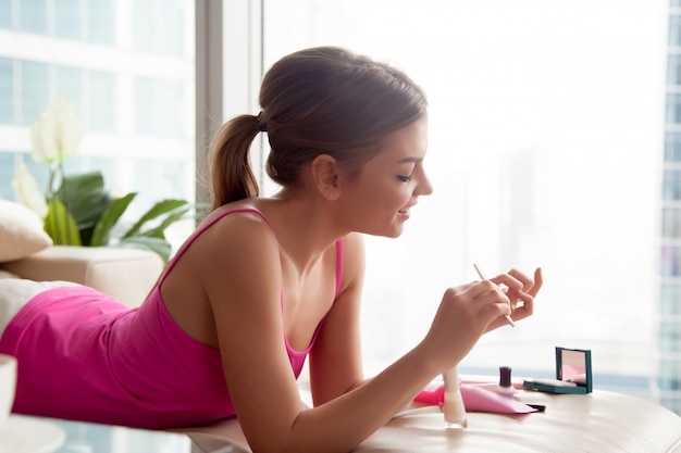 Mujer joven haciendo manicura en casa