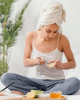 Mujer joven haciendo una mascarilla natural en casa