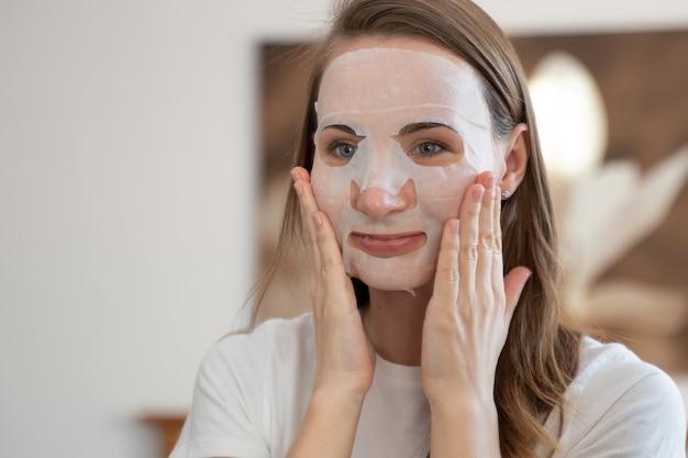 Mujer joven haciendo mascarilla purificante en su rostro
