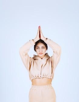 Mujer joven haciendo meditación y mostrando posturas de manos