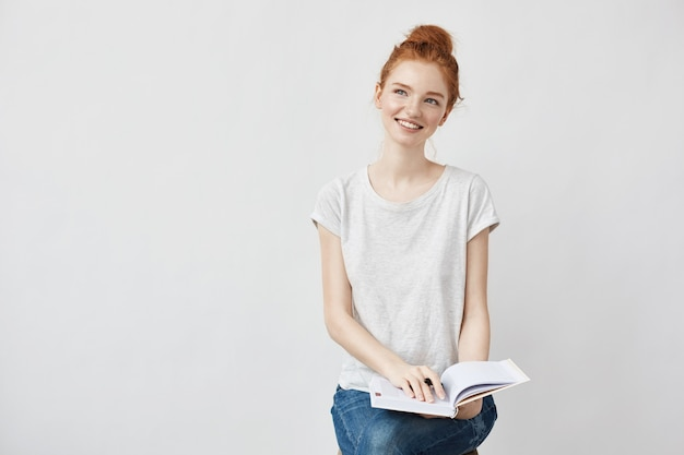 Mujer joven haciendo notas en el diario, sonriendo alegremente.