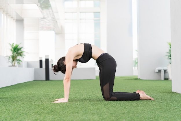 Mujer joven haciendo una pose de yoga en casa.