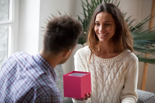 Mujer joven haciendo presente dando caja de regalo abierta a marido