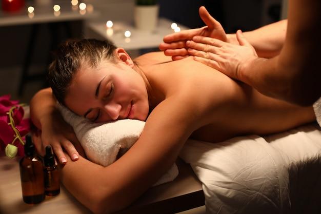 Mujer joven haciendo relajante masaje de espalda en el salón