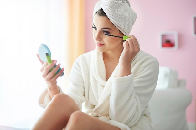 Mujer joven haciendo su maquillaje en la mañana
