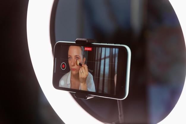 Mujer joven haciendo un vlog de maquillaje con su smartphone