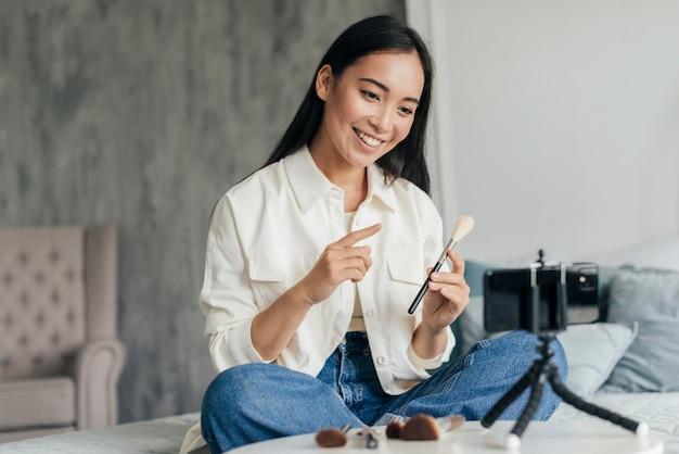 Mujer joven haciendo un vlog sobre maquillaje en interiores