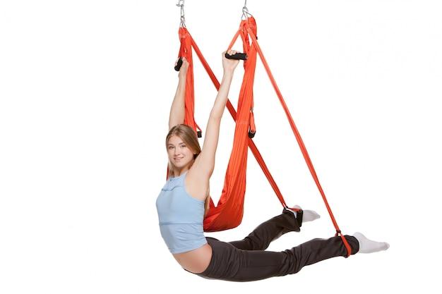 Mujer joven haciendo yoga aéreo antigravedad en hamaca roja sobre una pared blanca sin costuras