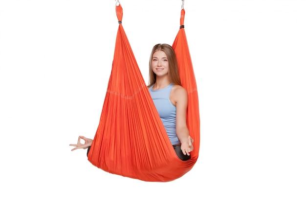 Mujer joven haciendo yoga aéreo antigravedad
