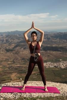 Mujer joven haciendo yoga al aire libre