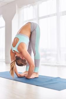 Mujer joven está haciendo yoga asana uttanasana - doblar hacia adelante en el estudio de yoga