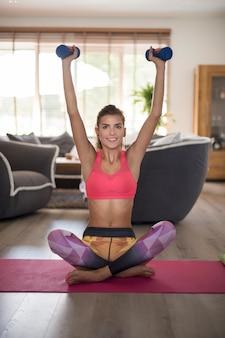 Mujer joven haciendo yoga en casa. manos fuertes es mi prioridad