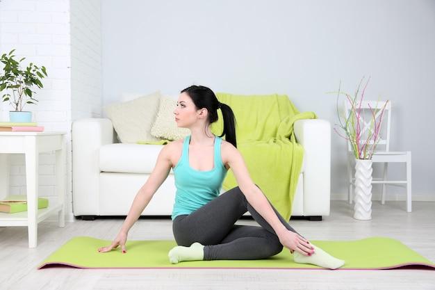 Mujer joven haciendo yoga en casa