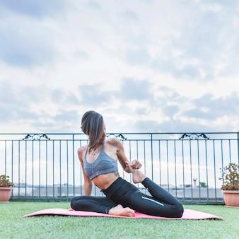 Mujer joven haciendo yoga por la mañana