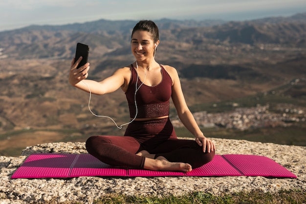 Mujer joven haciendo yoga en maqueta de montaña