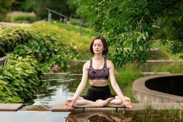 Mujer joven haciendo yoga. niña sentada en posición de loto en el parque cerca de un pequeño lago decorativo