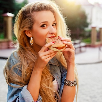 Mujer joven hambrienta comiéndose una sabrosa hamburguesa