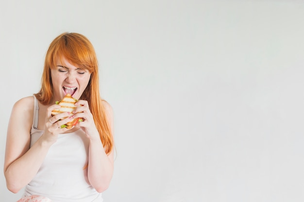 Mujer joven hambrienta que come el emparedado asado a la parilla contra el fondo blanco