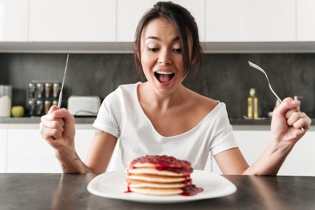 Mujer joven hambrienta sentada en la cocina en casa
