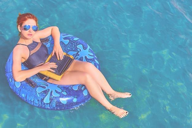 Mujer joven hermosa con un anillo inflable y una computadora portátil que se relajan en el mar.