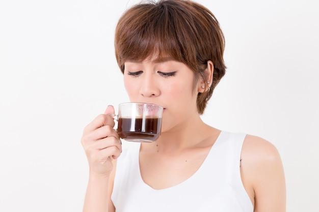 Mujer joven hermosa de asia con una taza de café caliente. concepto para la salud.