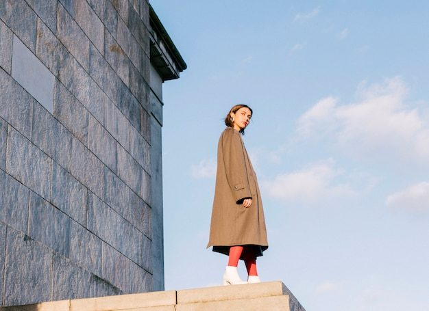 Una mujer joven hermosa atractiva que se coloca delante de la pared contra el cielo