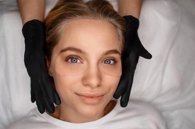 Mujer joven hermosa atractiva que miente nad que mira derecho. está segura. esteticista toca su rostro con las manos en guantes de látex negro.