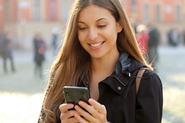 Mujer joven hermosa atractiva que usa el teléfono inteligente al aire libre en la ciudad