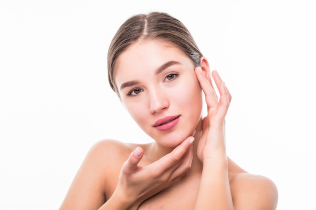 Mujer joven hermosa del balneario que toca su cara aislada en la pared blanca.