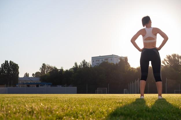 Una mujer joven, hermosa, de cabello oscuro, con un corte de pelo corto y una complexión atlética, se ejercita en el parque temprano en la mañana. concepto de estilo de vida saludable. yoga