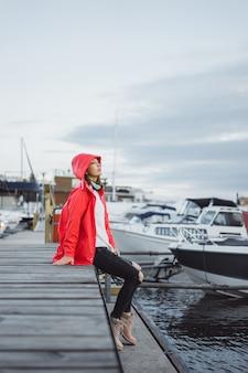 Mujer joven hermosa en una capa roja en el puerto del yate. estocolmo, suiza
