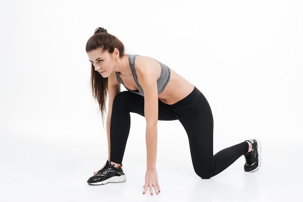 Mujer joven hermosa deporte comienza a correr aislado en un fondo blanco