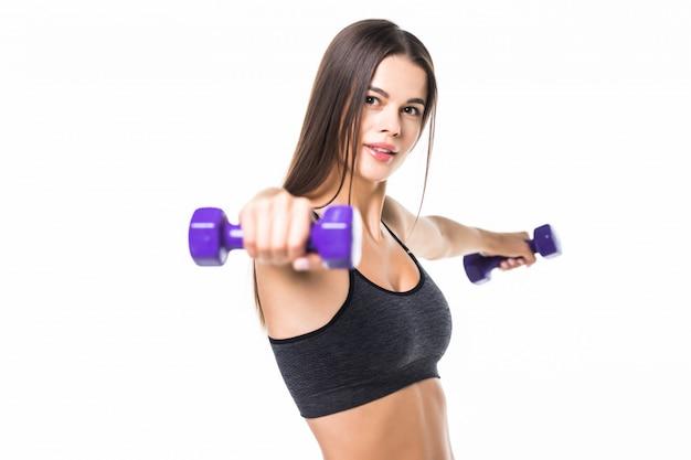 Mujer joven hermosa y deportiva que levanta para arriba pesos contra blanco.