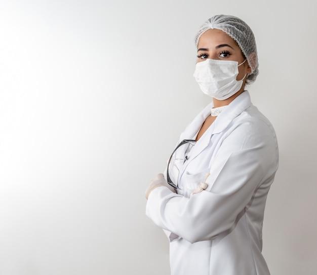 Mujer joven hermosa del doctor en capa blanca médica y una máscara protectora y guantes de goma.