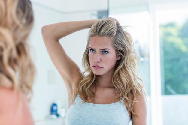 Mujer joven hermosa enfocada que se mira en el espejo del cuarto de baño en casa
