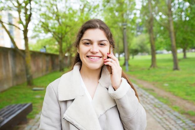 Mujer joven hermosa feliz que invita al teléfono en parque