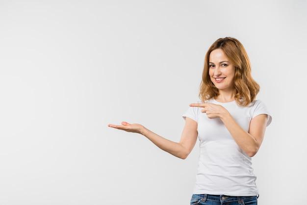 Mujer joven hermosa feliz que señala en algo a mano