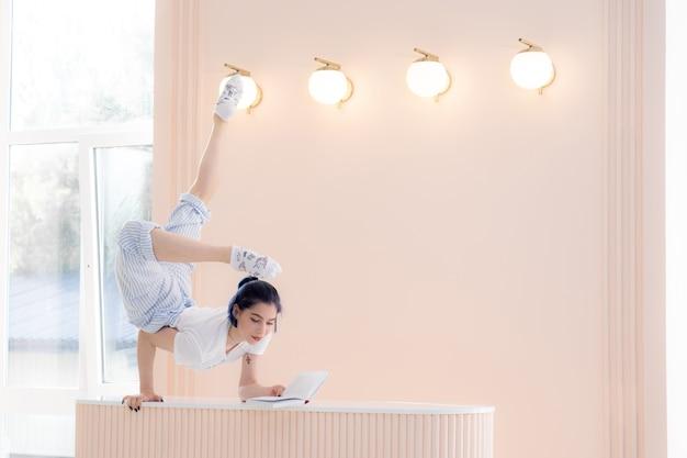 Mujer joven hermosa flexible que lee un libro en el escritorio en casa concepto de la creatividad de la individualidad ...