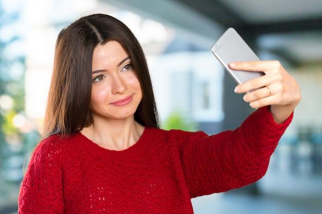 La mujer joven hermosa está haciendo la foto del selfie con smartphone