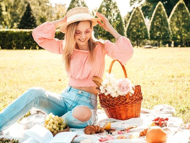 Mujer joven hermosa hipster en jeans de moda de verano, camiseta rosa y sombrero. mujer despreocupada haciendo picnic afuera.